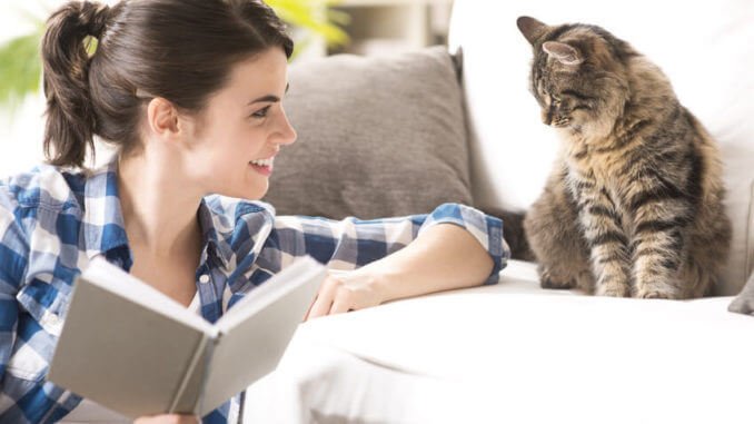 Eine Frau hält ein aufgeschlagenes Buch in der Hand und lacht ihre Katze an, die auf dem Sofa sitzt