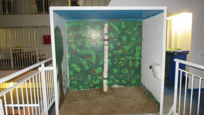 Eine große nach oben geöffnete Kiste mit Sandboden und einem gemalten Wald an den Wänden