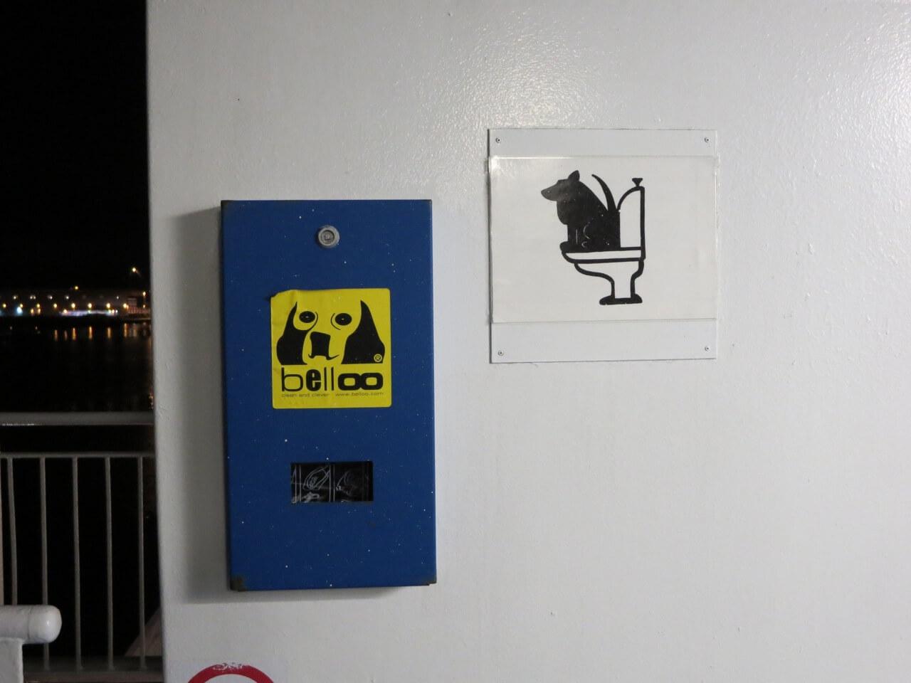 Ein Schild mit einem Hund auf einer Toilette und eine Box mit Abfallbeuteln für das Geschäft