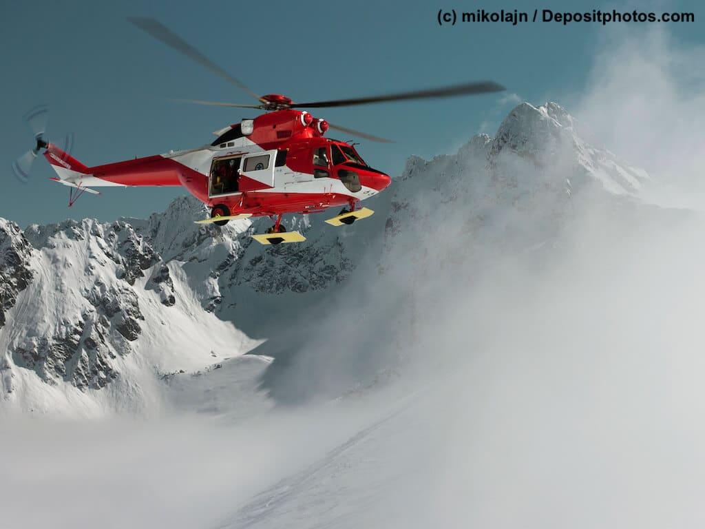 Ein rotweißer Helikopter steuert verschneiten Berghang an