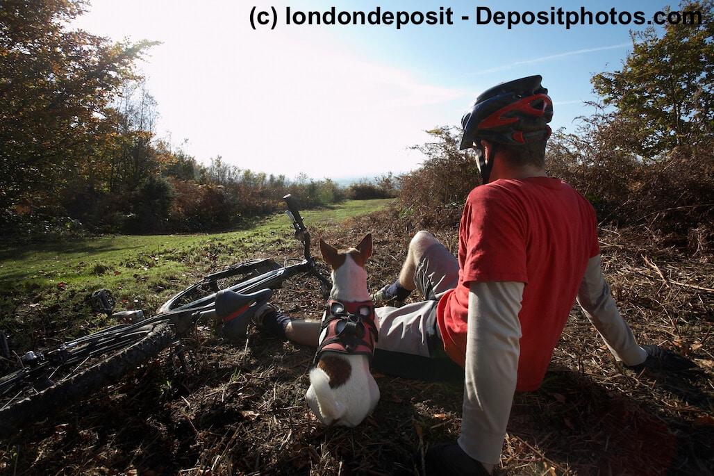 Ein Mountain biker und sein Hund sitzen nebeneinander und schauen in die Landschaft