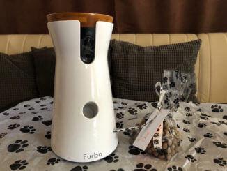 Die Hundekamera Furbo auf einem Tisch daneben ein Päckchen Leckerlies