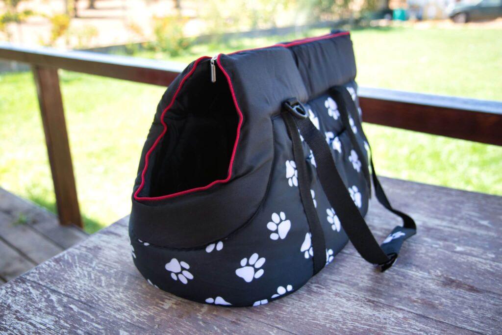 Unsere getestete Hundetragetasche von Hobbydog ist aus Polyester, schwarz mit weißem Pfotendruck und roten Nähten.