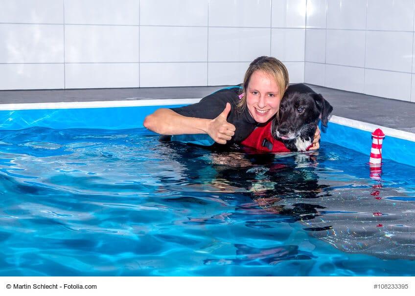 Frau mit Hund und Hundeschwimmweste im Physiotherapie Pool