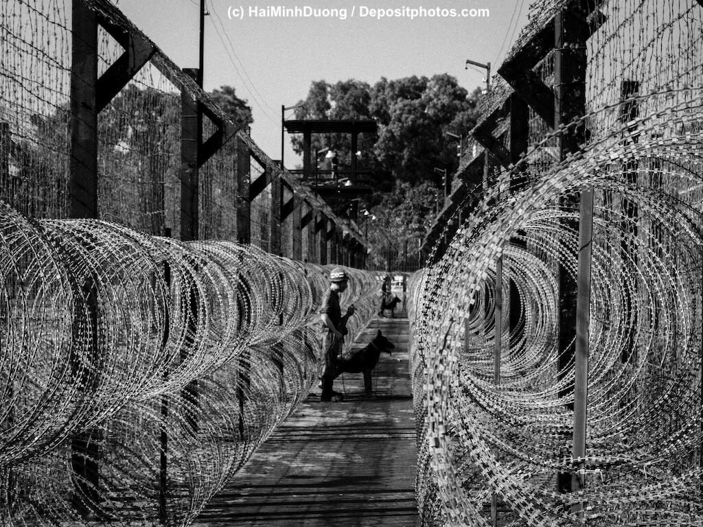 Stacheldrahtzäune an Gefängnis werden von Wachhund gesichert