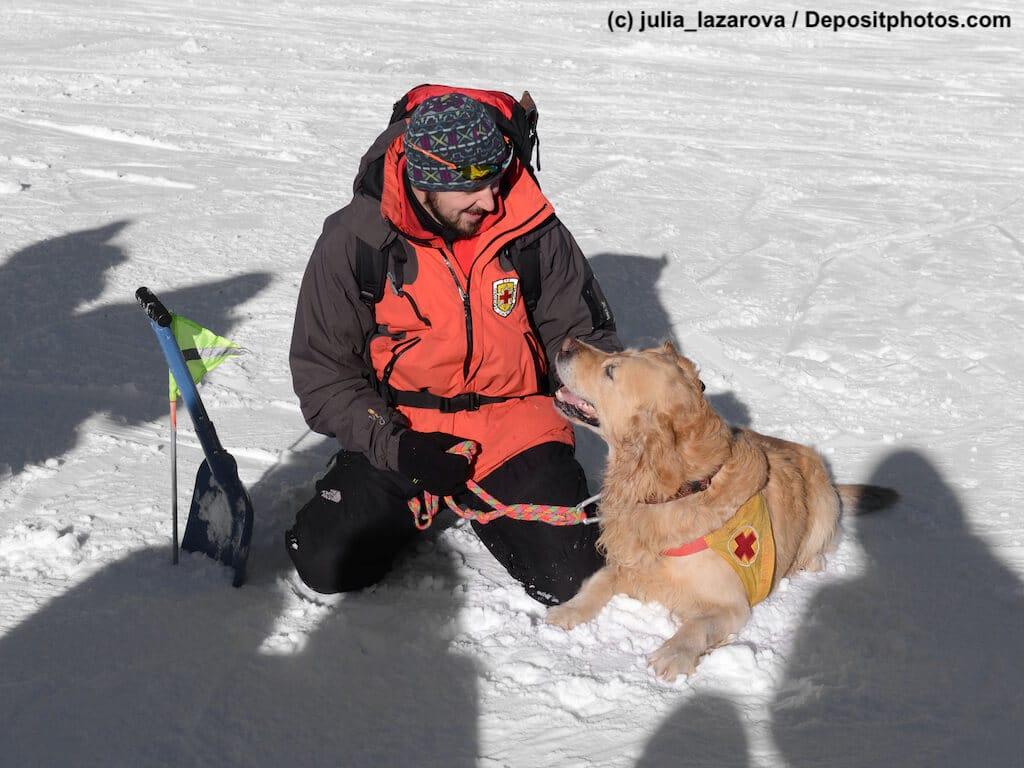 Lawinenretter und sein Hund im Schnee schauen sich an.