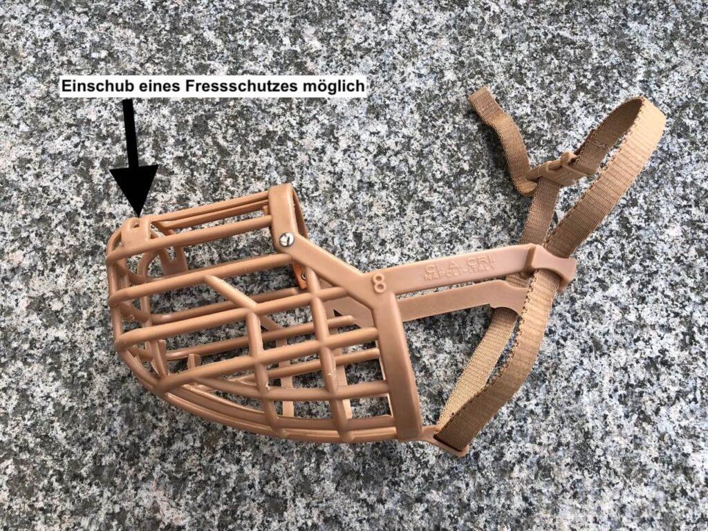 Baskerville Maulkorb mit herausgenommenem Fressschutz in Größe 8 seitlich auf Steinen liegend