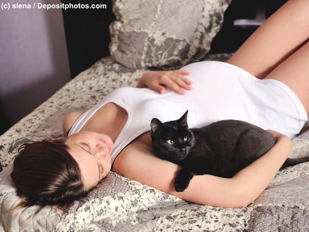 Eine schwangere Frau liegt lächelnd auf einem Bett in ihrem Arm liegt eine schwarze Katze