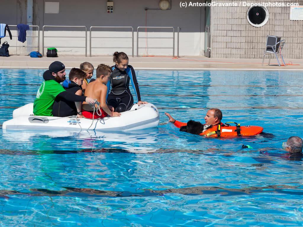 Schwimmbadtraining, Menschengruppe in Schlauchboot, Rettungsschwimmer mit Hund im Wasser.