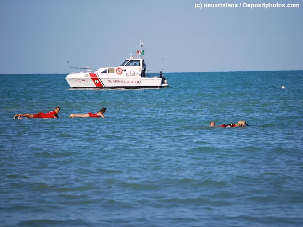 Rettungsschwimmer mit Schiff und Hund im Meer.