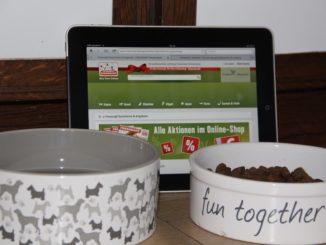 Zwei Fressnäpfe und im Hintergrund ein iPad mit der Seite von Fressnapf online.