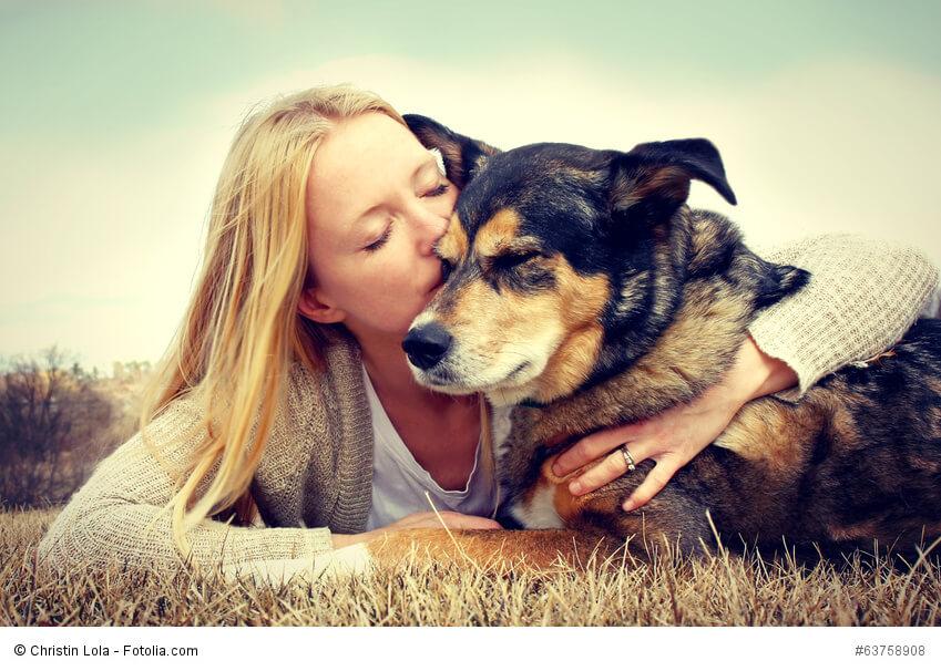 Eine blonde junge Frau umarmt und küsst ihren Deutschen Schäferhund