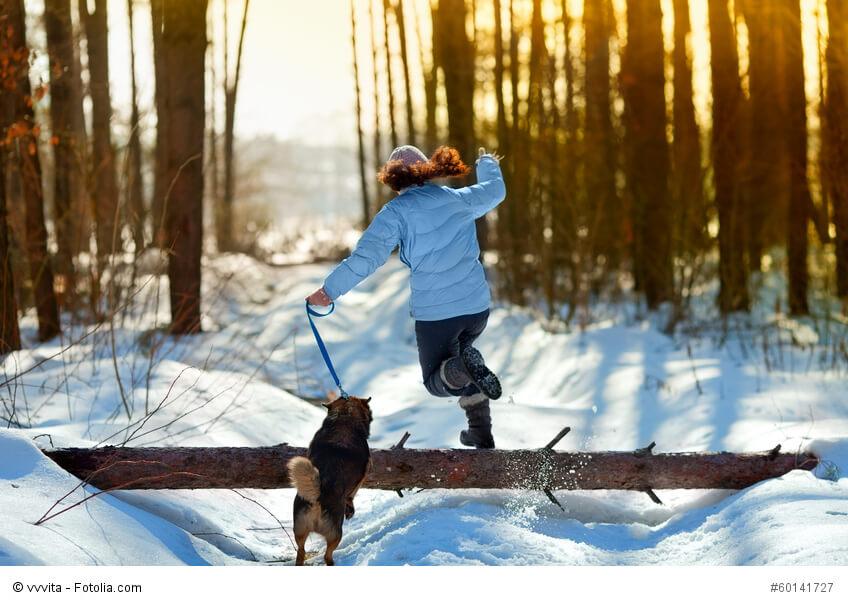 Eine junge Frau springt mit ihrem Hund an der Leine über einen Baumstamm im Schnee