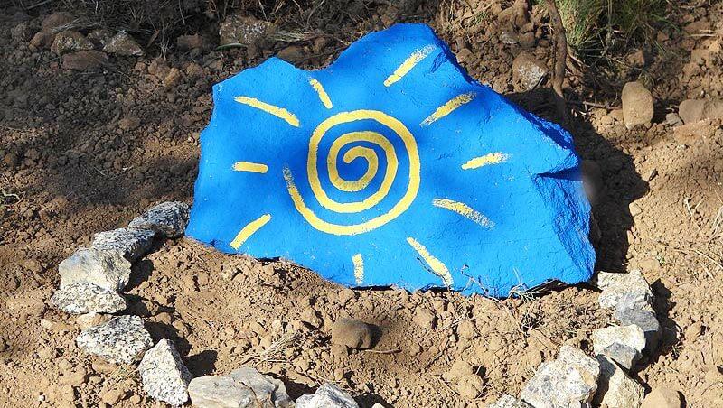 Ein blauer Stein, auf den eine gelbe Sonne gemalt ist