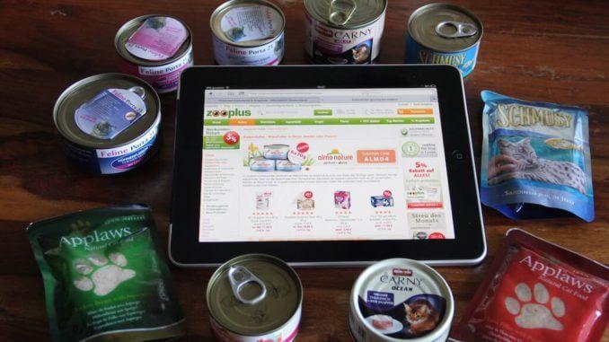 IPad mit der Zooplus-Seite zwischen Futterdosen und -tüten.
